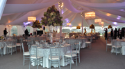 Custom fabric draping and carpeted flooring with silver chiavari chairs